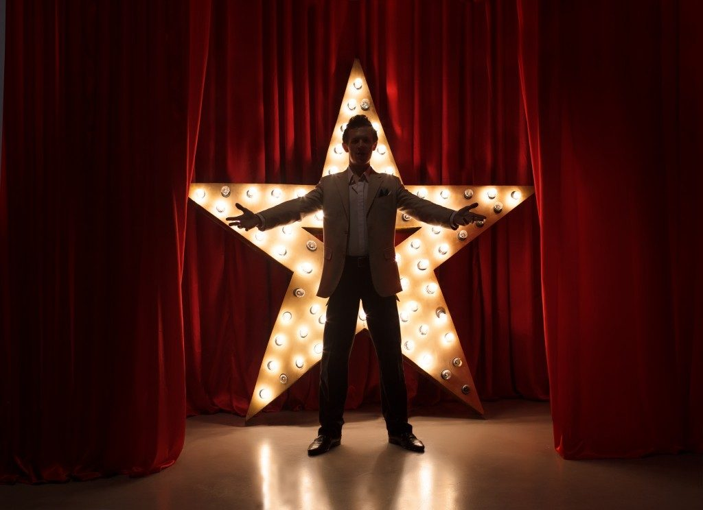 Man on theater stage with star on background