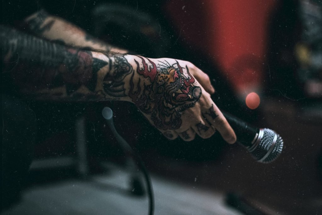 tattooed person holding mic
